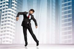 Puppet businessman. Image of businessman hanging on strings like marionette against city background. Conceptual photography stock photos