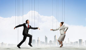 Puppet businesspeople. Image of businesspeople hanging on strings like marionettes against city background. Conceptual photography stock photo