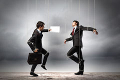 Puppet businesspeople. Image of businesspeople hanging on strings like marionettes. Conceptual photography stock photos