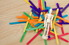 Puppet and colored wood sticks. On top wooden table Royalty Free Stock Photography