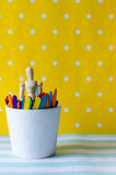 Puppet and colored wood sticks. In white cup on colorful background Royalty Free Stock Photo
