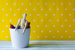 Puppet and colored wood sticks. In white cup on colorful background Royalty Free Stock Image