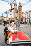 Puppet of Elvis Presley entertaining people in Krakow, Poland. Puppet of Elvis Presley entertaining people on the Main Market Square with St. Mary's Church in Royalty Free Stock Images