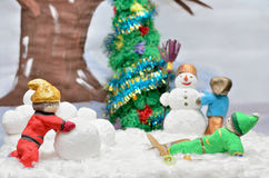 Puppet figures of children mold the snowman. Royalty Free Stock Images