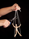 Puppet freedom. Hand cutting the strings of a puppet, giving it freedom Royalty Free Stock Photos