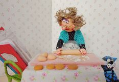 Puppet granny cooking cookies. Cold porcelain clay sculpted puppets Royalty Free Stock Photography