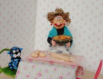 Puppet granny cooking cookies. Cold porcelain clay sculpted puppets Stock Images