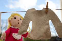 Puppet hanging out clothes. A cute woman puppet hanging out a jumper on a washing line Royalty Free Stock Photos