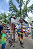 Puppet Jester. A young girl is captivated by a puppet jester at the Bristol Renaissance Faire in Wisconsin Stock Photography