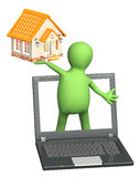 Puppet with laptop and house. Isolated over white Royalty Free Stock Images