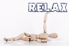 Puppet laying at ground, with its right arm up. Holding the word `RELAX stock photo