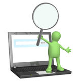 Puppet with magnifier and laptop Stock Images