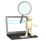 Puppet with magnifier and laptop Royalty Free Stock Images