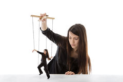 Puppet master. Business woman holding a puppet of herself pulling strings Royalty Free Stock Photo