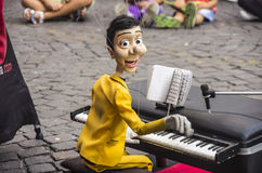 Puppet pianist. A funny puppet dressed in a yellow elegant suit playing the piano and singing Stock Photo