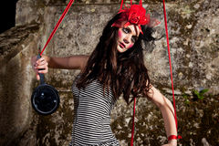Puppet on a string. Beautiful girl wearing red hat and striped skirt posing as a marionette (puppet on a string stock photos