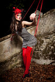 Puppet on a string. Beautiful girl wearing red hat and striped skirt posing as a marionette (puppet on a string Royalty Free Stock Photography