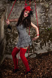 Puppet on a string. Beautiful girl wearing red hat and striped dress posing as a marionette (puppet on a string stock photo