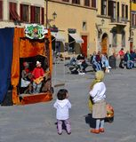 Puppet theater. Children watching at a funny puppet theater in the street. The shot has been taken in Florence, Italy royalty free stock image