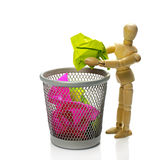 Puppet throw paper in trash can. Wooden puppet throw crumpled paper in trash can stock image