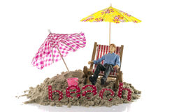 Puppet toy man sitting in chair on the beach Royalty Free Stock Photos