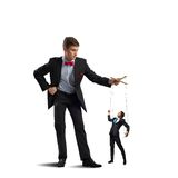 Puppeteer and puppet business. Puppeteer holds the puppet business men on the ropes stock image