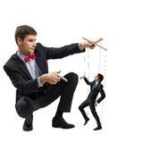 Puppeteer and puppet business. Puppeteer holds the puppet business men on the ropes stock images