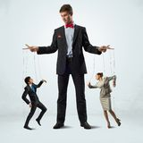 Puppeteer and puppet business. Puppeteer keeps business people puppets, concept control business stock photography