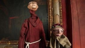 Puppets dressed as monks next to framed art stock video footage