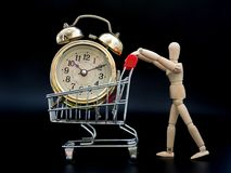 Puppets are holding a shopping cart. There is a golden vintage clock inside on black background. the concept of buying times.  Royalty Free Stock Photo