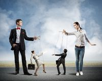 Puppets and puppeteers business. Puppeteers holding the strings of puppets business, business concept control stock photo