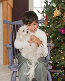 Puppy for Christmas. A handsome young boy sitting near his Christmas tree delighted with the puppy he holds on his lap Stock Photos