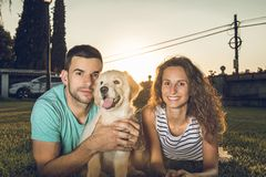 Puppy dog next to a couple of boyfriends. Concept of love between dogs and people. Labrador retriever puppy breed stock photography