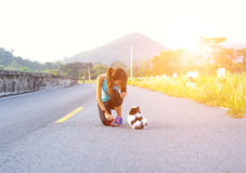 Puppy dog and young women running exercise on the street park in the morning Stock Photo