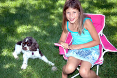Puppy and girl 1. Young girl setting in chair with puppy laying on grass royalty free stock images