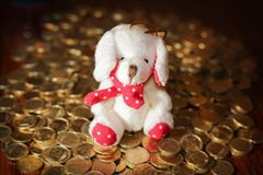 Puppy on gold coins - a symbol of wealth. The symbol of the new year is a dog on gold coins. The concept - wealth and prosperity, well-being. Very cute doggy toy Stock Photography