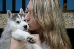 Puppy Kisses. Woman holding Husky puppy in her arms Royalty Free Stock Image