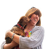 Puppy licks. Photo of a woman laughing as her puppy licks her cheeks whilst getting a puppy cuddles Royalty Free Stock Images
