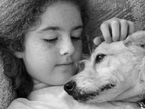 Puppy Love. A black & white image of a girl petting her dog. They are looking lovingly at each other Stock Photo