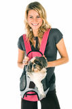 Puppy Love. Happy young woman who is a loving pet owner carrying her dog in a front carry pet carry bag royalty free stock image