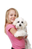 Puppy Love. A little girl with her first puppy on white background.Maltese Puppy Stock Photography