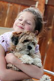 Puppy Love. A little girl hugging and adoring her puppy. Shallow depth of field Stock Image