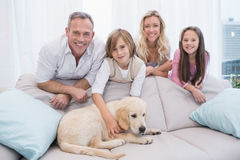 Puppy lying on the couch with the family standing behind Royalty Free Stock Photo