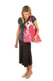 Puppy Purse. Happy young woman who is a loving pet owner carrying her dog in a big pink pet purse and blowing kisses to th dog Royalty Free Stock Photo
