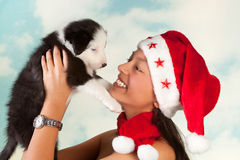 Puppy and santa girl Stock Images