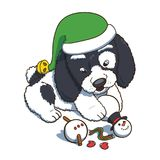 Puppy Wearing a New Year Elf Hat Plaing with Snowman Stock Photo