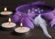 Puprple dream catcher on wooden background. Purple dream catcher on wooden background with lit candles. Focus at first candle Stock Images