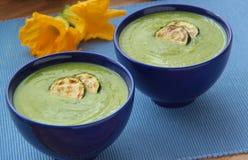Purè di verdure della zuppa di zucchine con le fette arrostite di zucchini Fiori dello zucchini su fondo Chiuda sulla vista Immagini Stock