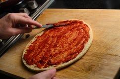 Puré de extensión del tomate de la mano en base de la pizza Imágenes de archivo libres de regalías