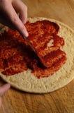 Puré de extensión del tomate de la mano en base de la pizza Imagenes de archivo